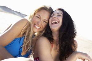 blonde and brunette girls laughing at the beach