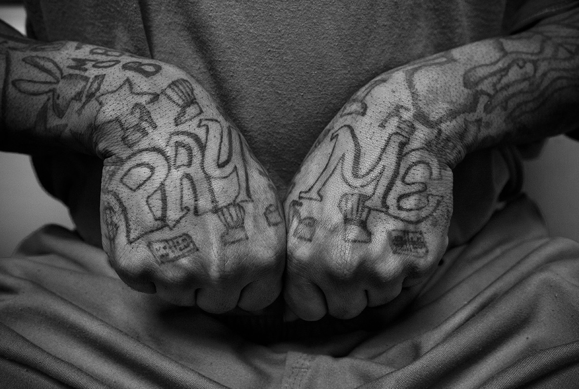 man with hand tattoos in black and white